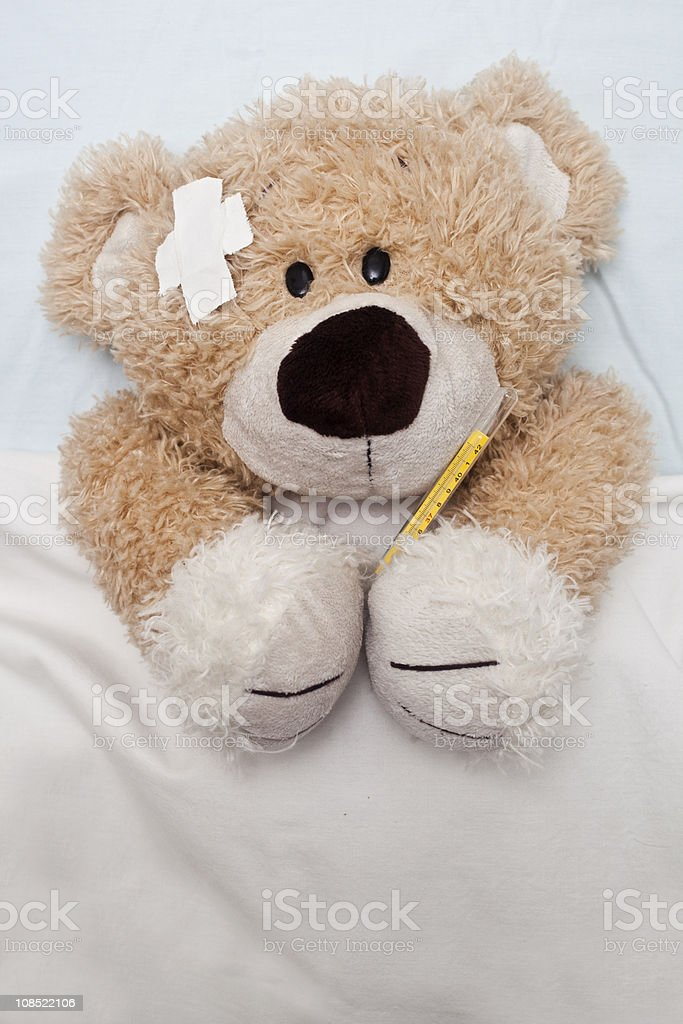 Cute teddy bear laying in bed royalty-free stock photo