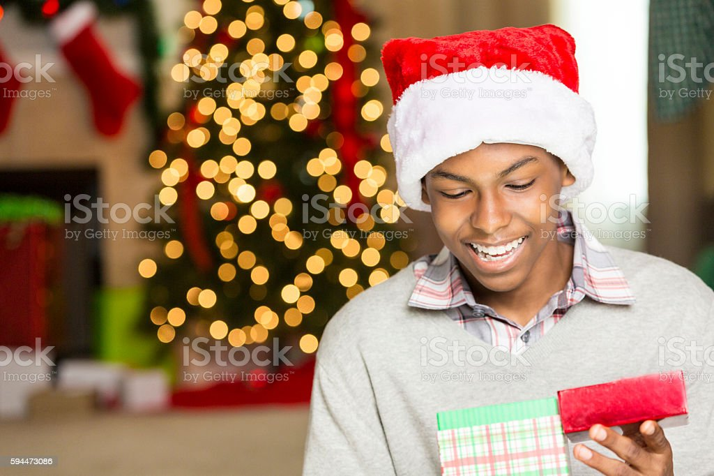 Cute teen boy opens gift on Christmas day stock photo