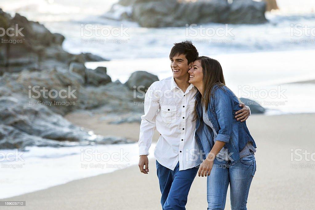 Jolie teen couple marchant le long de la plage. photo libre de droits