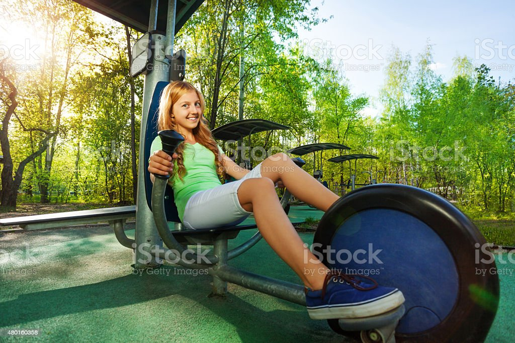 Cute teenage girl cycling on exercise equipment stock photo