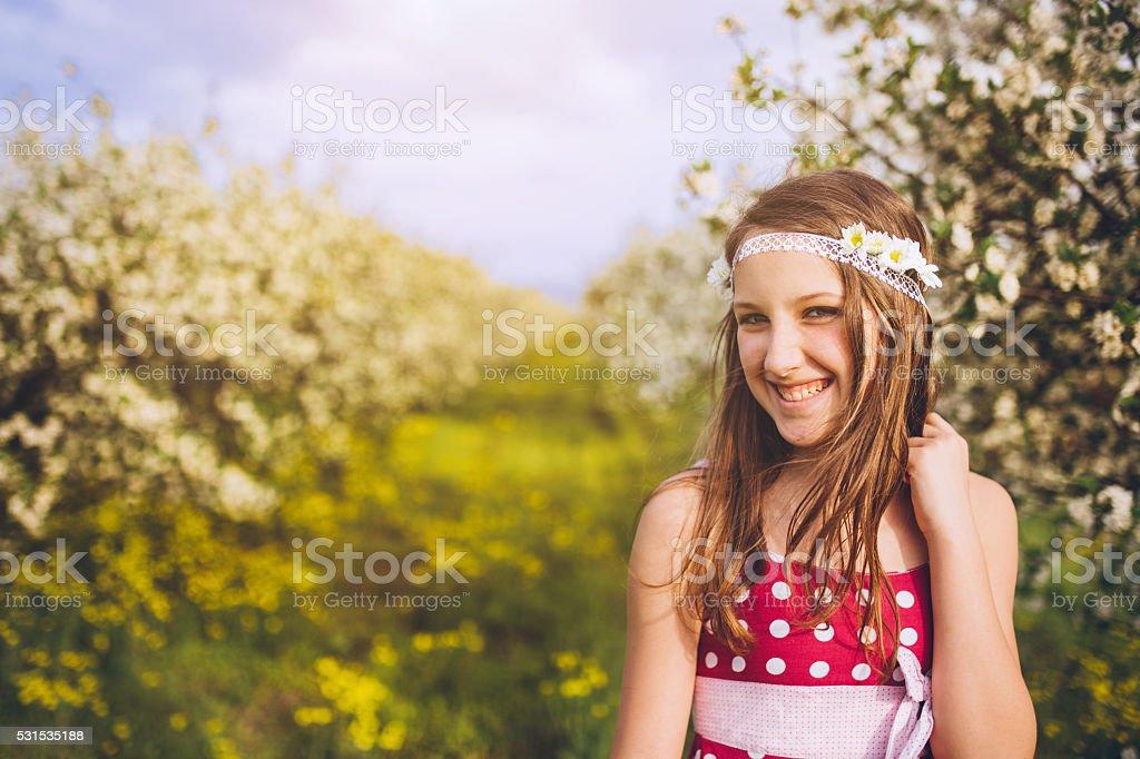 Cute teenage girl standing in cherry blossom garden stock photo