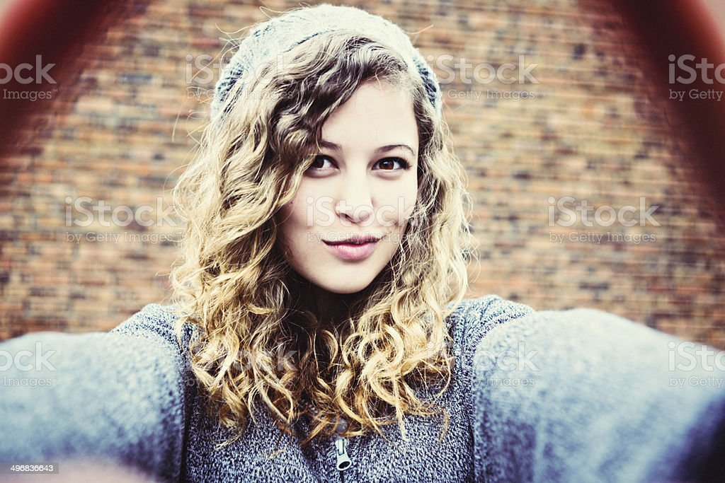 Cute teenage girl takes flirtatious, smiling Selfie stock photo