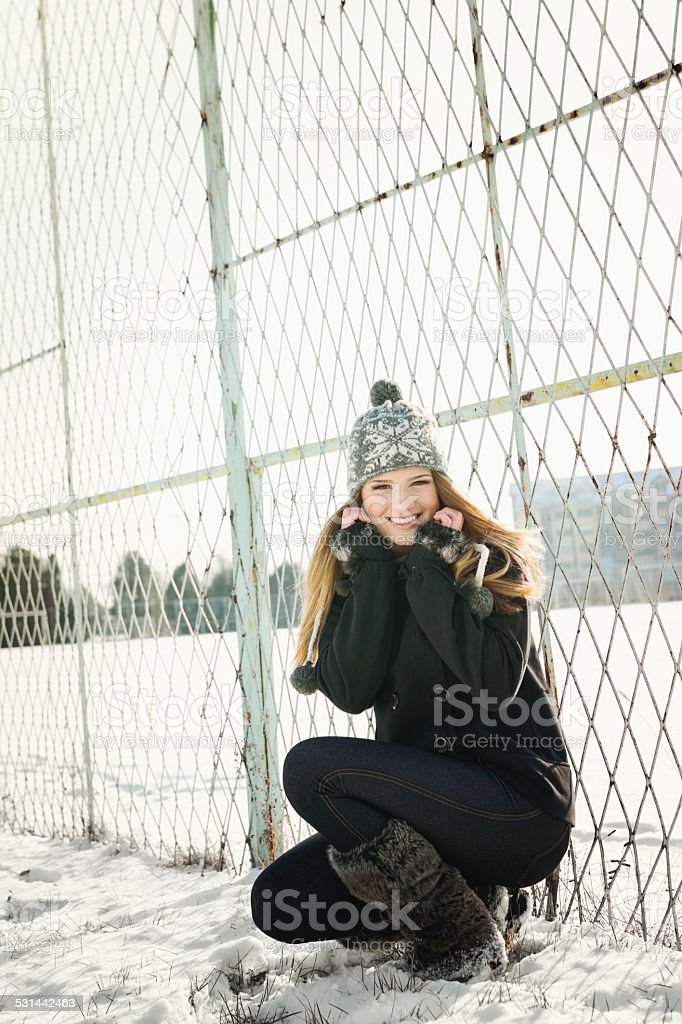 Cute teenage girl with hat in park in winter stock photo