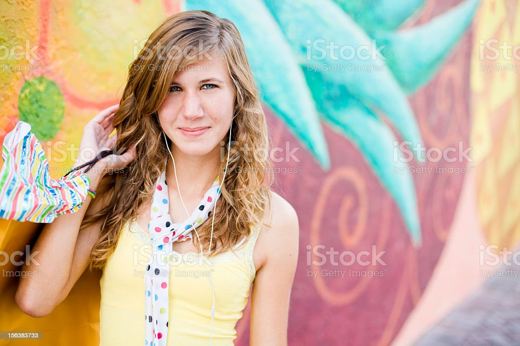cute teenage girl with headphones on holding shopping bag royalty-free stock photo