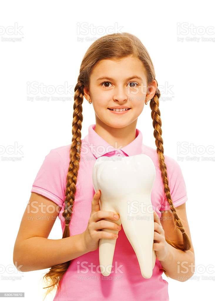 Cute teenager holding tooth dummy in her hands stock photo