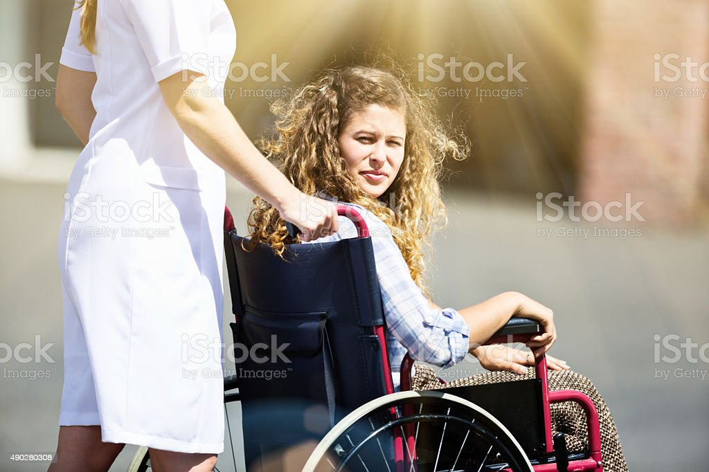 Cute teenager in wheelchair turns around, smiling stock photo