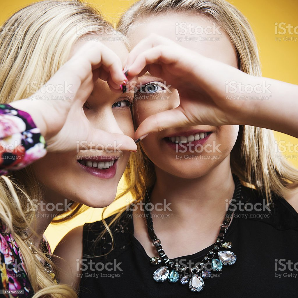 Cute teenagers doing a heart frame royalty-free stock photo
