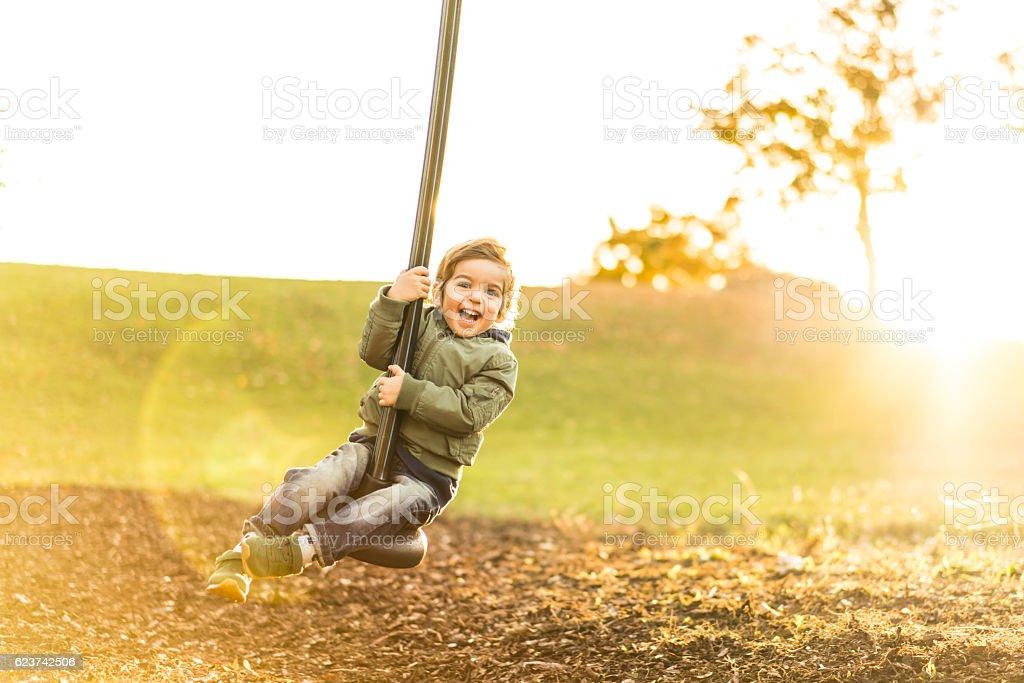 cute three year old boy on a zipline in backlight stock photo