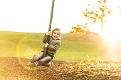 cute three year old boy on a zipline in backlight