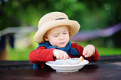 Cute toddler boy eating rice cereal outdoors