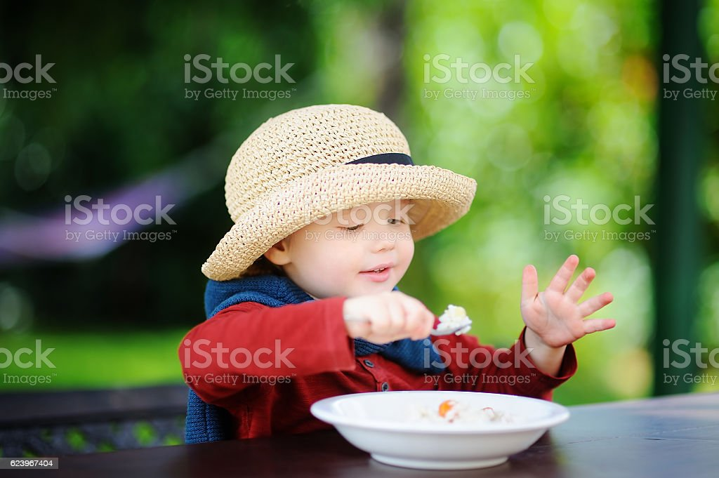 Cute toddler boy eating rice cereal outdoors stock photo