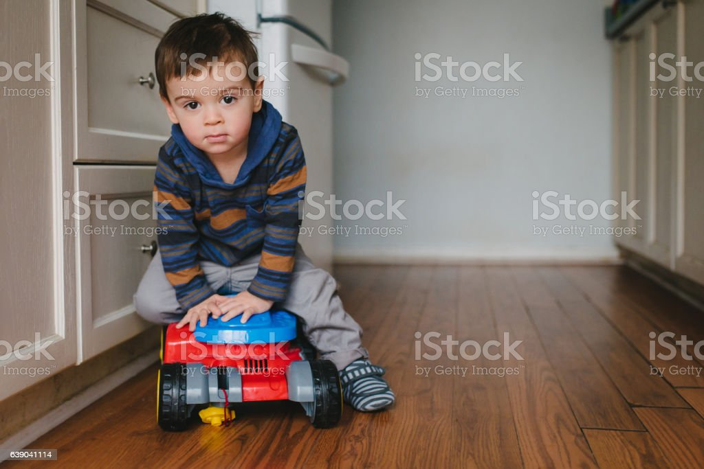 Cute Toddler Boy Playing in the Kitchen stock photo