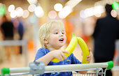 Cute toddler boy sitting in the shopping cart with bananas