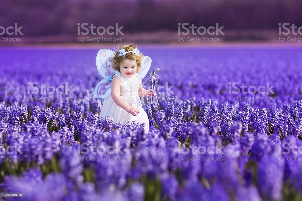 Cute toddler girl in fairy costume playing on flower field stock photo