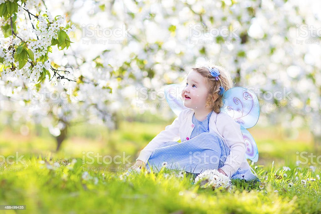 Cute toddler girl in fairy costume under cherry blossom trees stock photo
