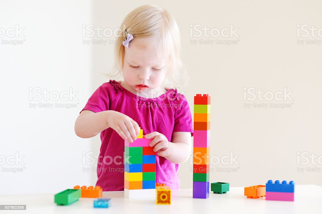 Cute toddler girl playing with colorful blocks stock photo