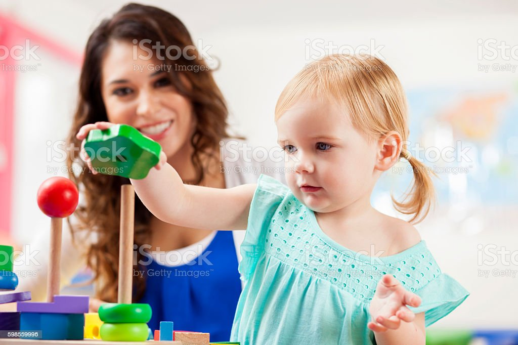 Cute toddler girl playing with learning blocks in daycare stock photo
