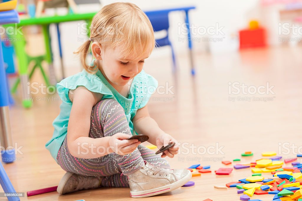 Cute toddler girl playing with toys on daycare floor stock photo