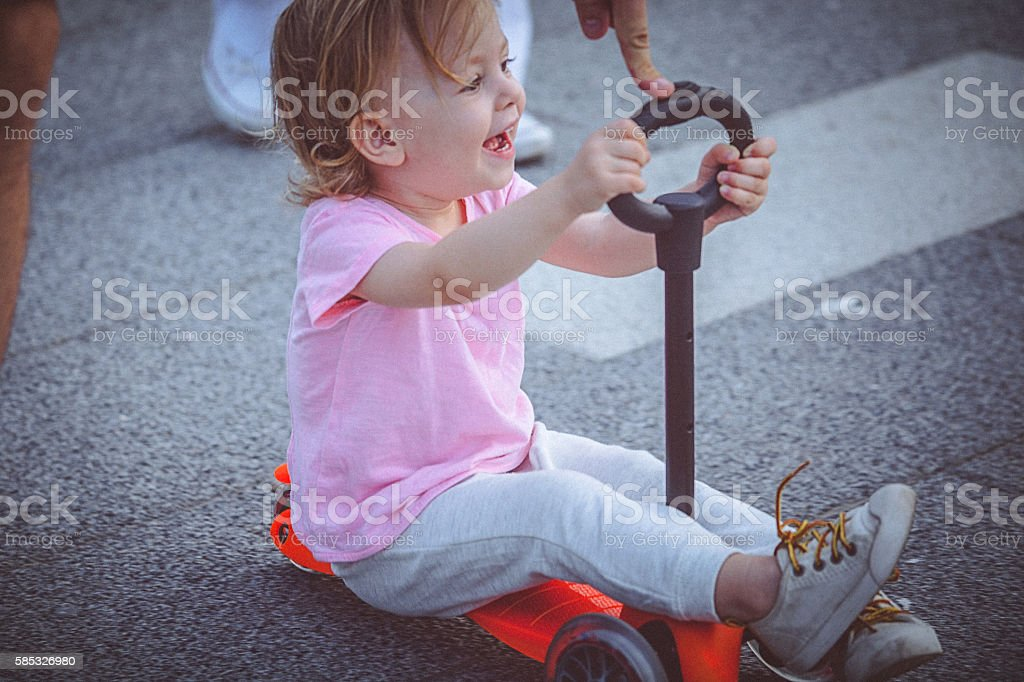 Cute toddler girl rides push scooter on the promenade stock photo