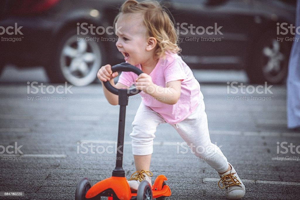 Cute toddler girl riding push scooter on the city street stock photo