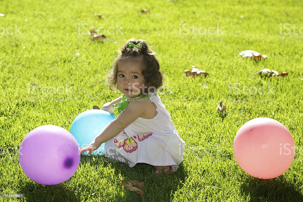 Cute Toddler Girl Sitting on the Grass with Balloons royalty-free stock photo
