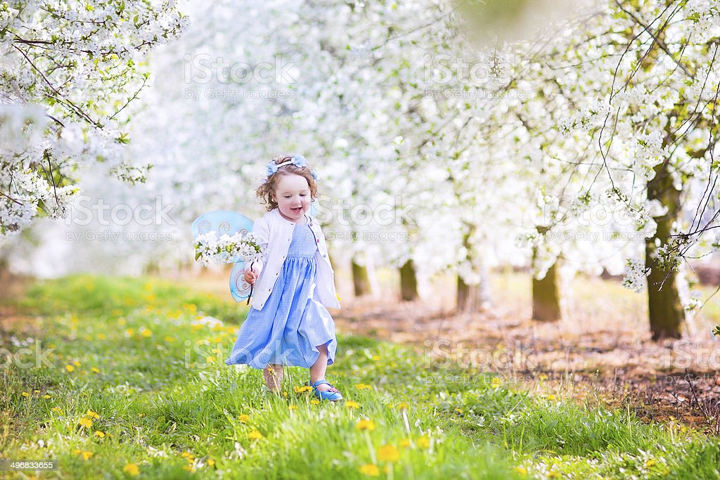 Cute toddlger girl wearing fairy costume playing in blooming garden stock photo