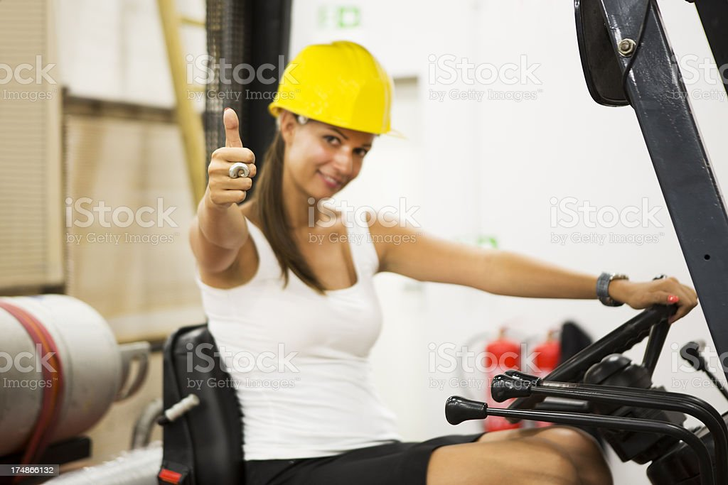 Cute warehouse worker in a fork lift...thumb up royalty-free stock photo