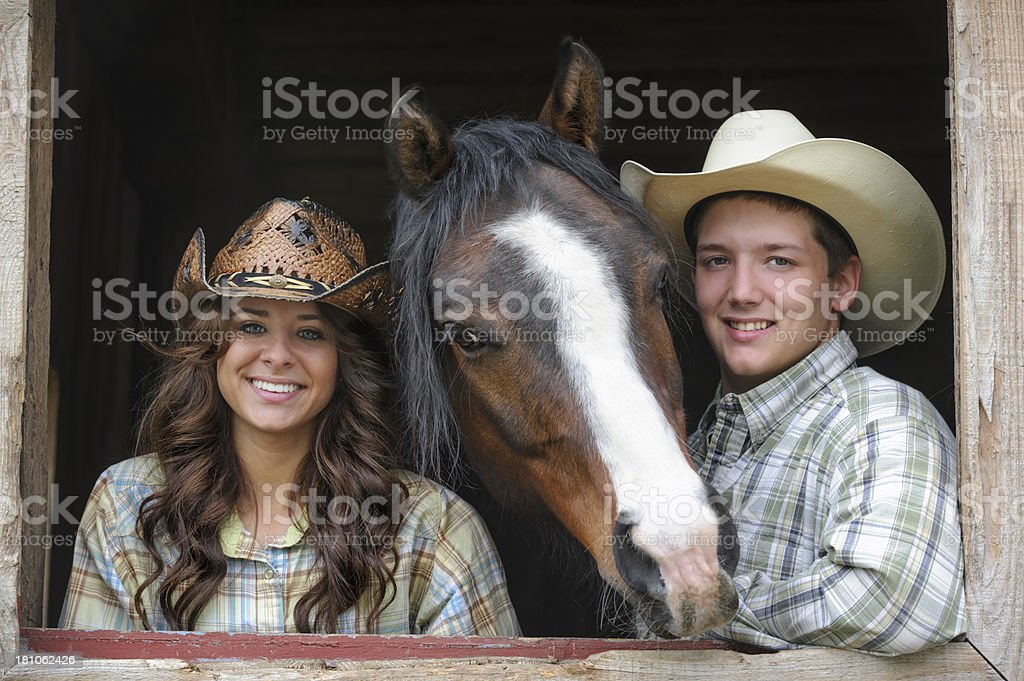 Cute Western Couple and Horse in Barn Window, Young Americans royalty-free stock photo