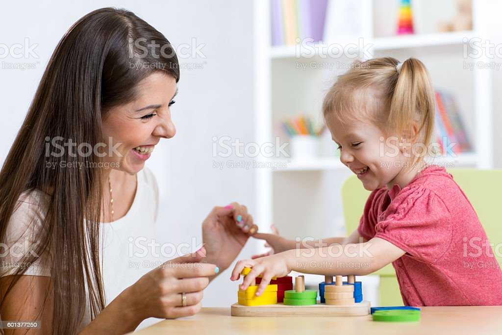 Cute woman and kid girl playing educational toys at home stock photo