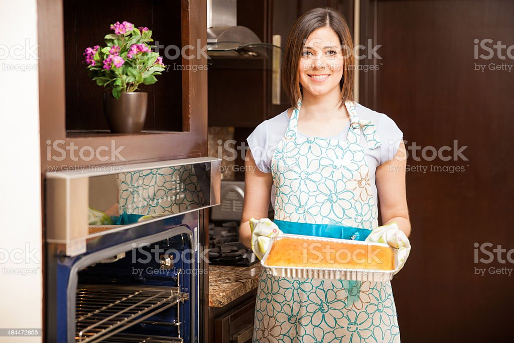 Cute woman baking a cake at home stock photo