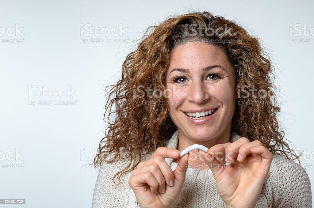 Cute woman breaking a cigarette stock photo