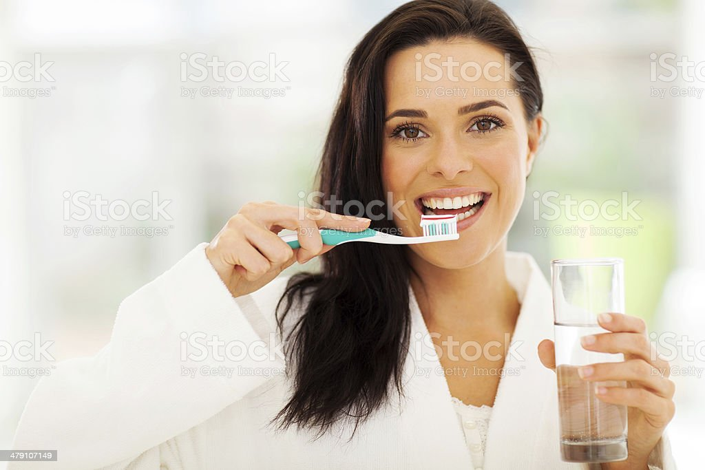 cute woman brushes her teeth stock photo