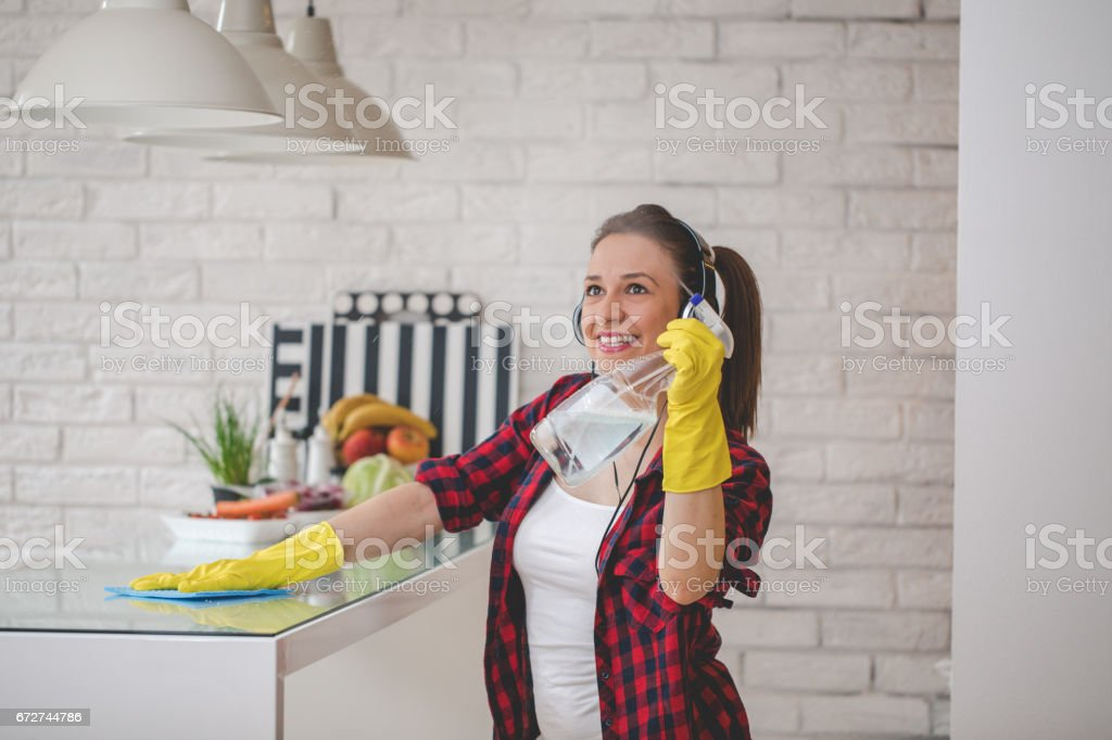 Cute woman cleaning kitchen stock photo