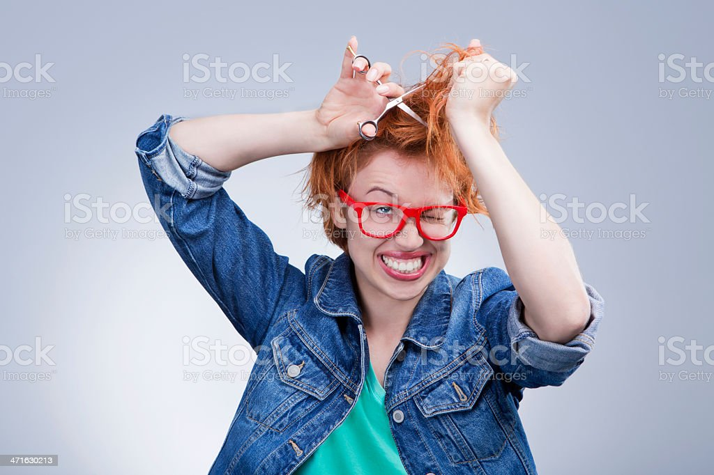 Cute woman cuts her hair with scissors Hairdressing royalty-free stock photo