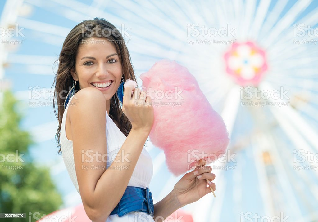 Cute Woman eating Cotton Candy at the Funfair stock photo
