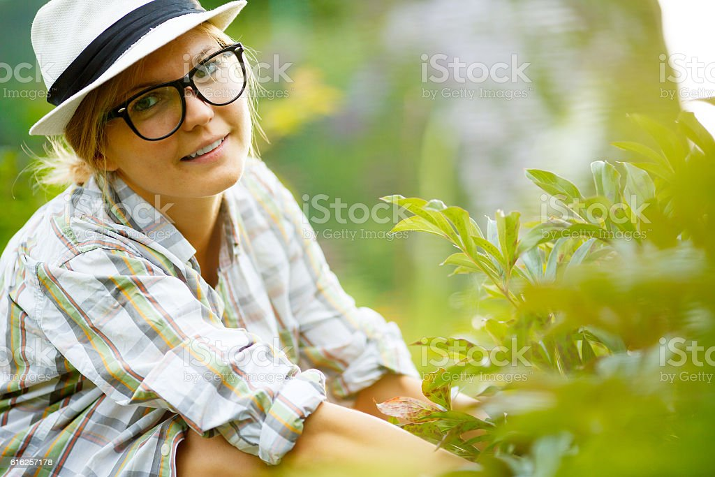 Cute woman gardener in hat and glasses working in garden stock photo