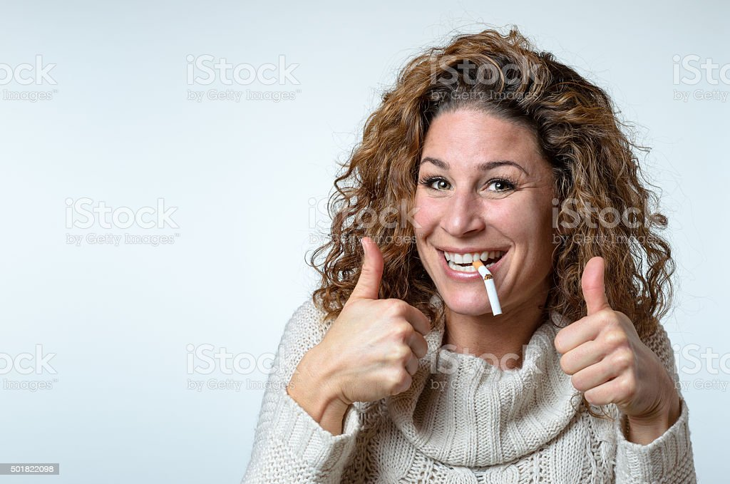 Cute woman giving a thumbs up gesture stock photo