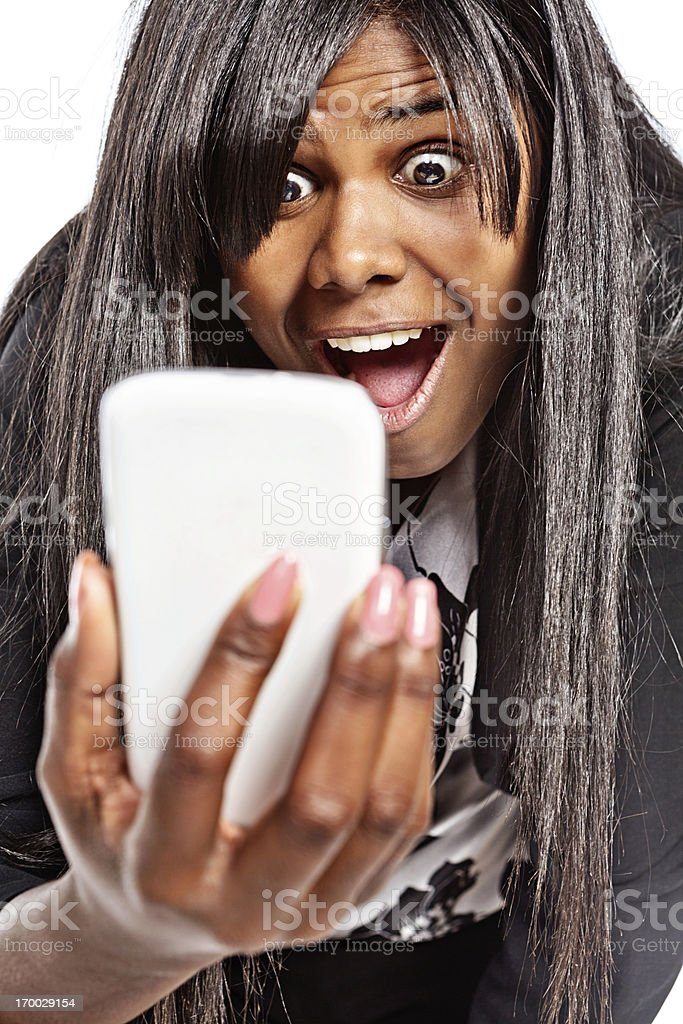 Cute woman is utterly shocked by something on mobile phone royalty-free stock photo