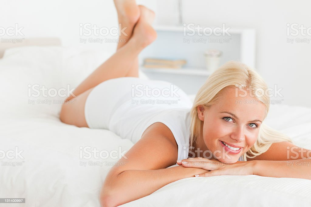 Cute woman lying on her bed royalty-free stock photo