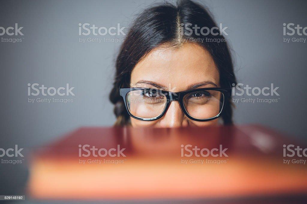 Cute woman peeking behind books stock photo