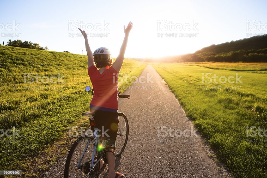 Cute Woman Riding Her Bike Down Sunlit Trail- Arms Raised stock photo