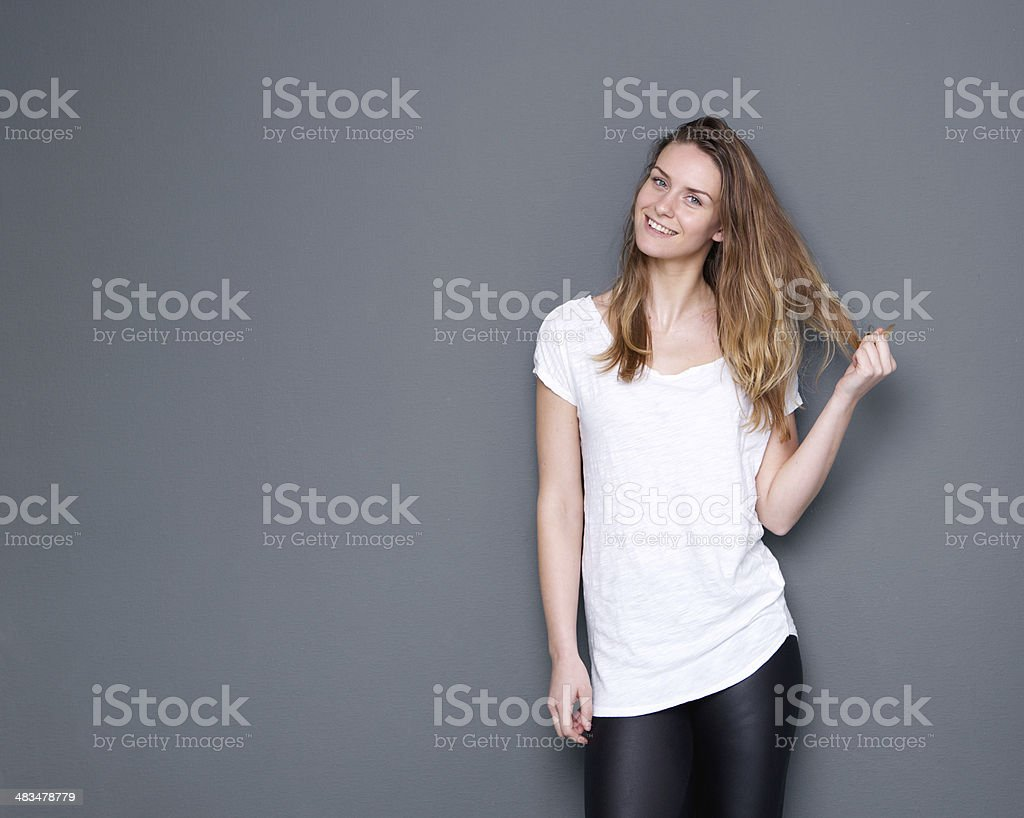 Cute woman smiling with hand in hair stock photo