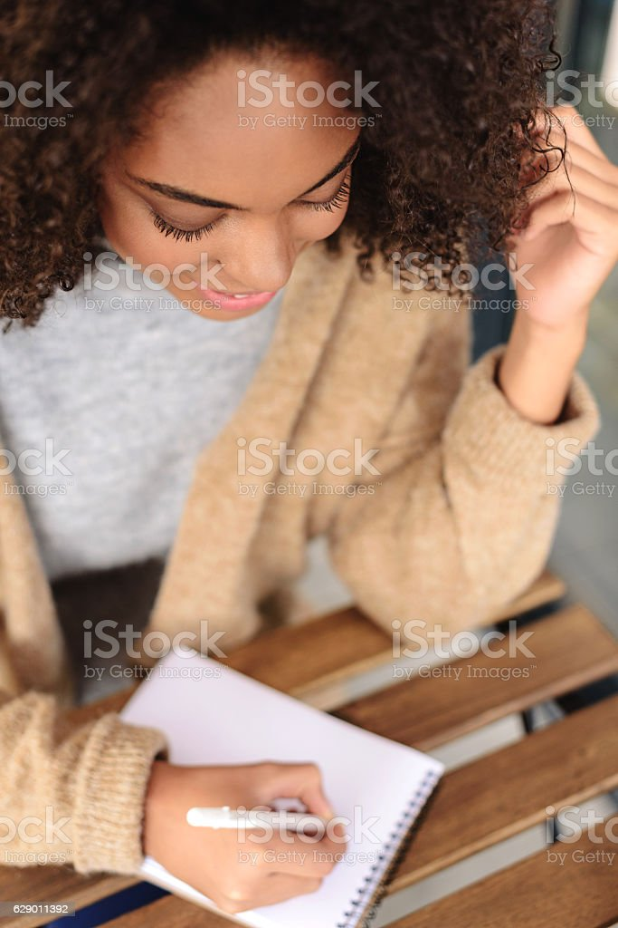 cute woman taking notes indoors stock photo