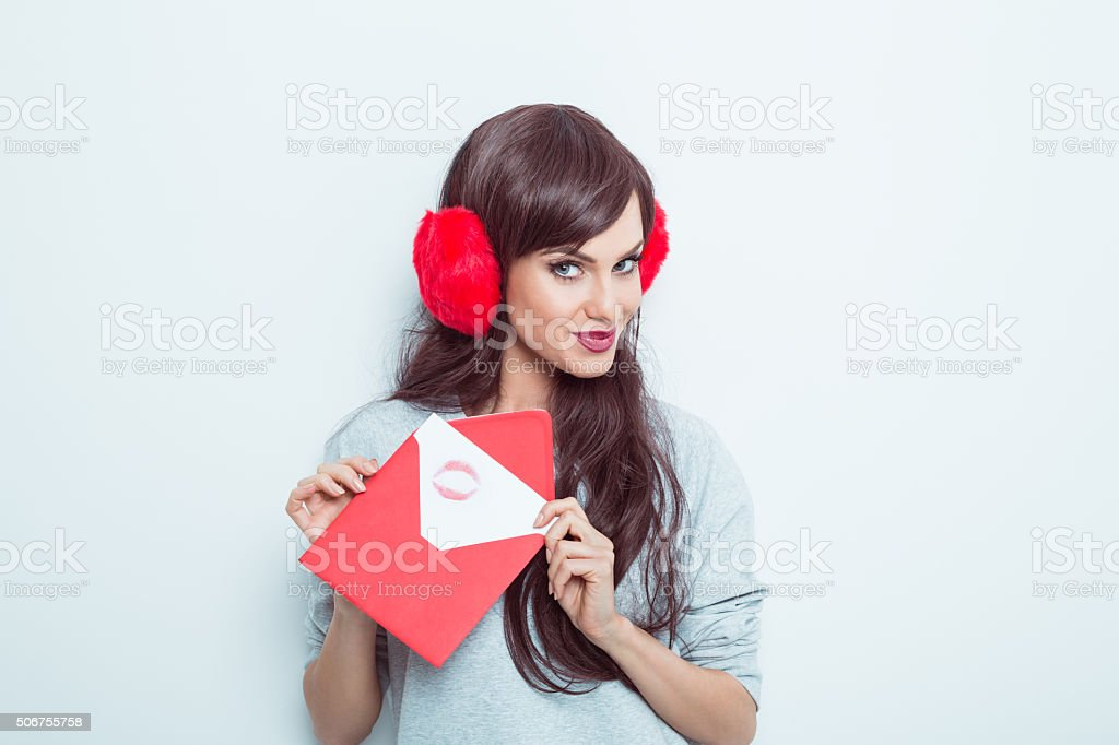 Cute woman wearing earmuffs holding love letter stock photo
