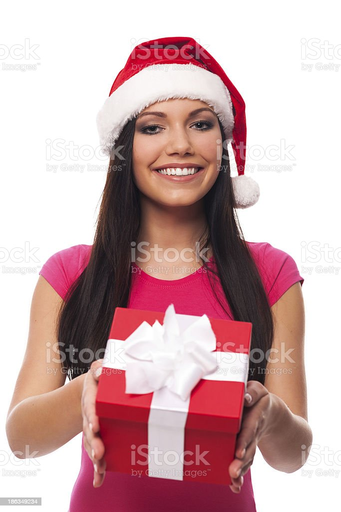 Cute woman with santa hat giving christmas gift royalty-free stock photo