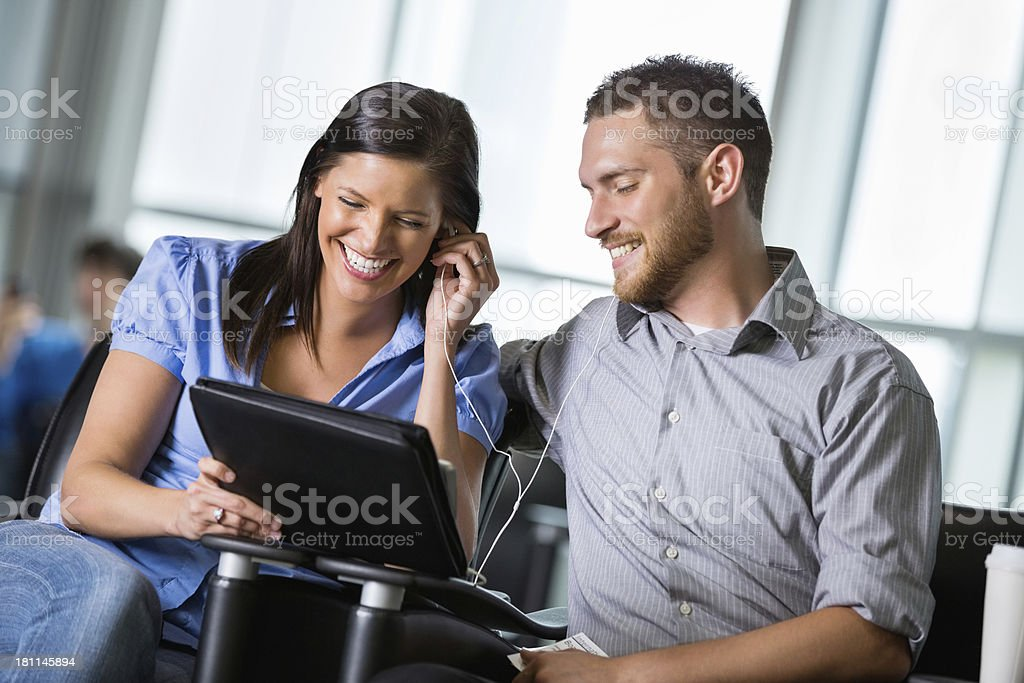 Cute young adult couple using tablet device in waiting area royalty-free stock photo