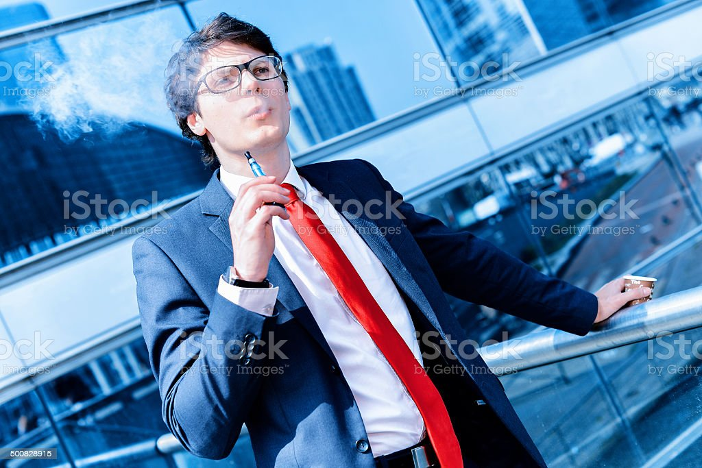 Cute young adult man inhaling from an electronic cigarette royalty-free stock photo