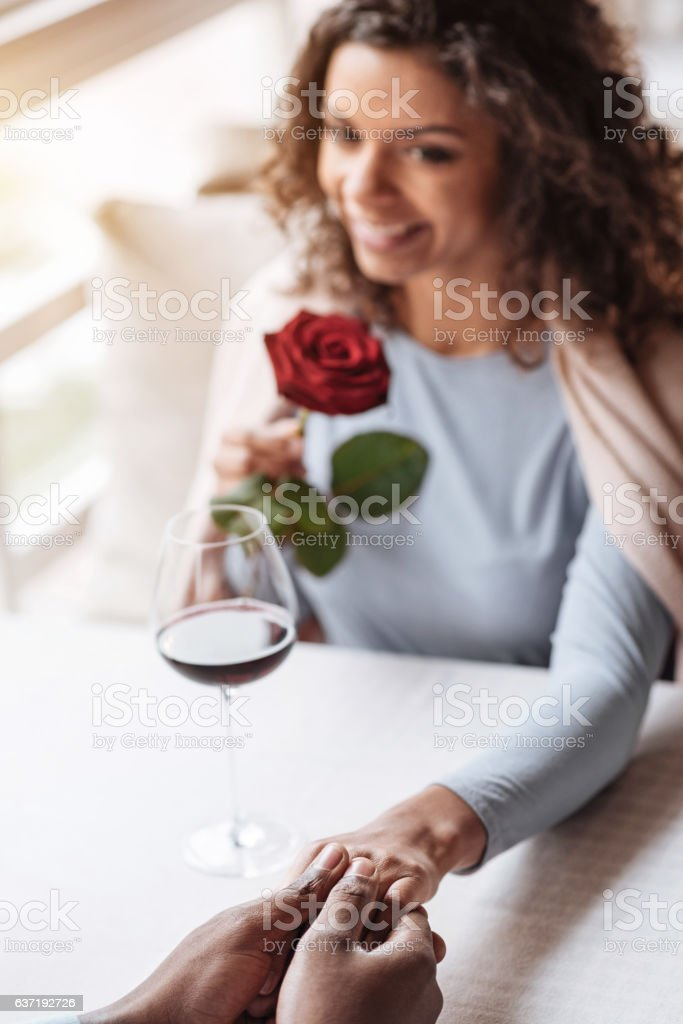 Cute young African American woman holding hands with her boyfriend stock photo