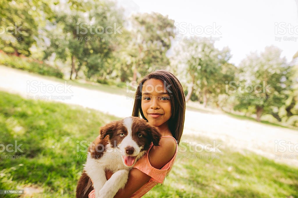 Cute young African-American long haired brunette girl cuddling a stock photo