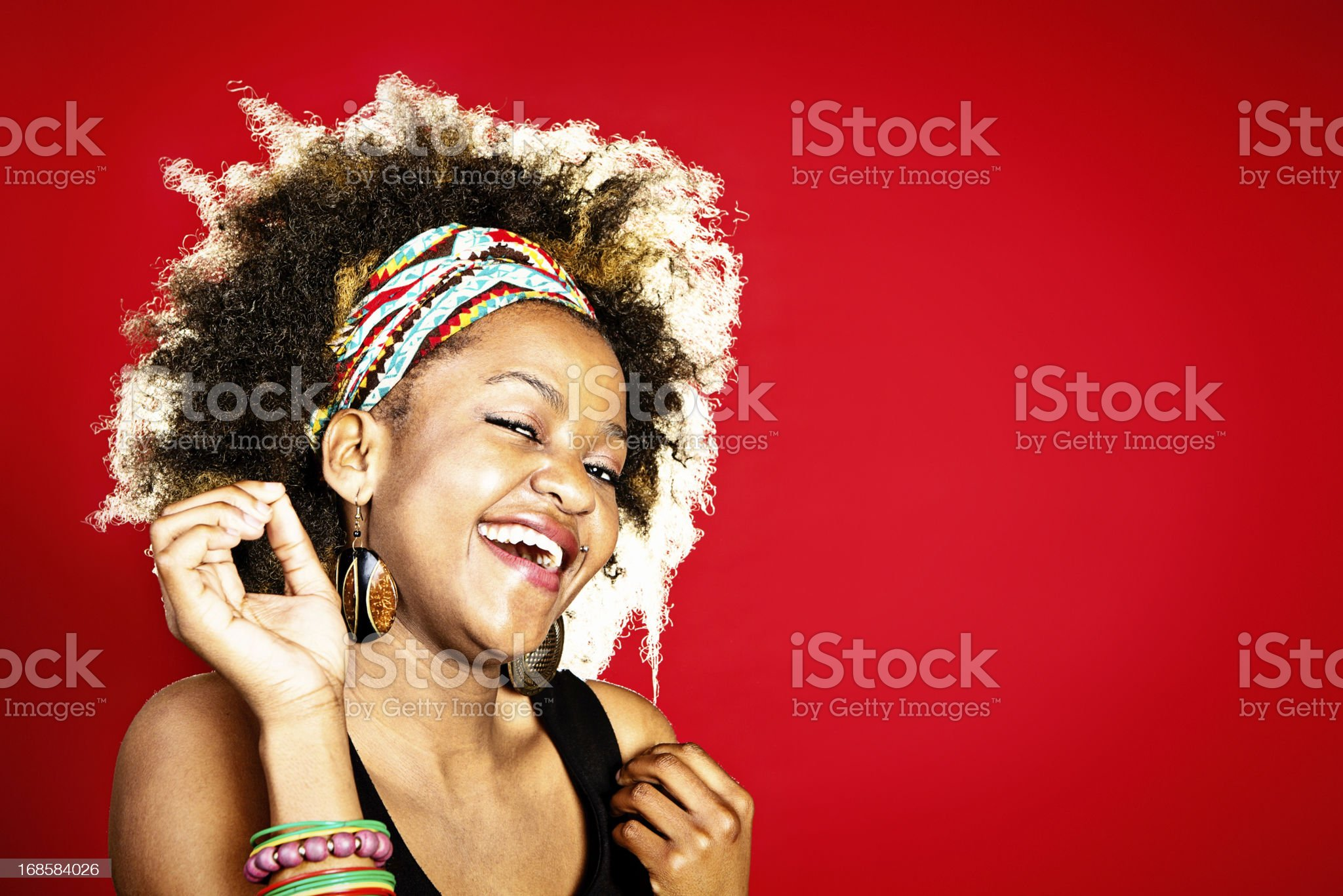 Cute young Afro-haired woman smiles and winks royalty-free stock photo